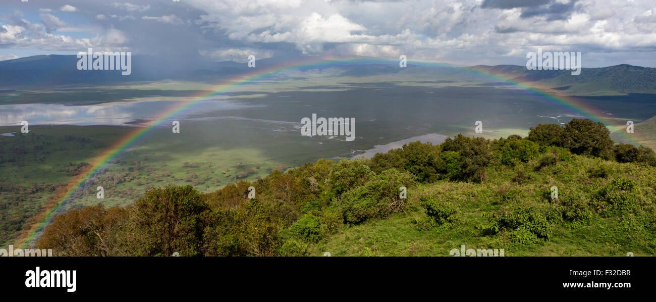 Panoramic view of rainbow at Ngorongoro Crater, Serengeti, Tanzania from Ngorongoro Wildlife Lodge on the crater's - Stock Image