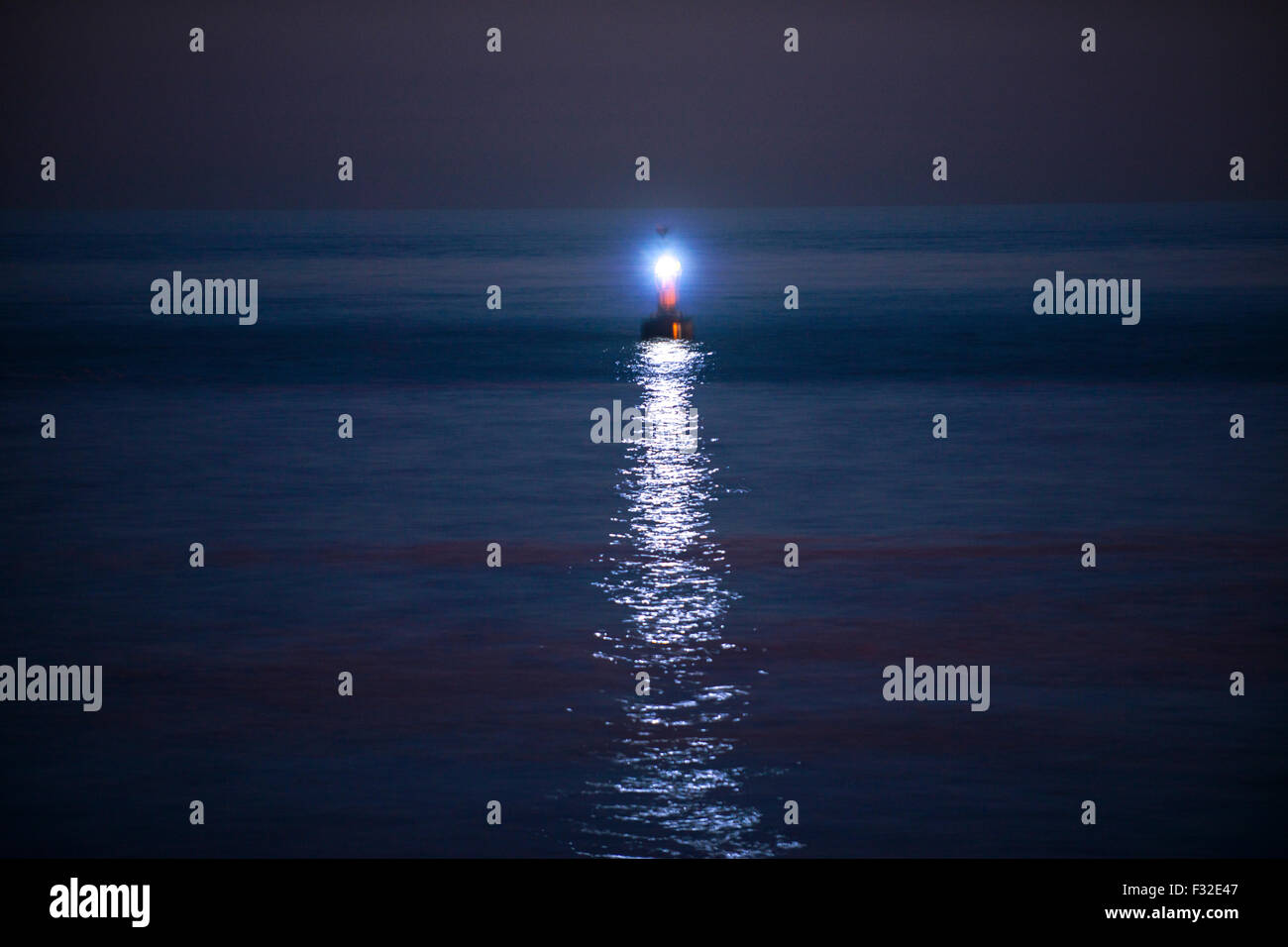Navigation buoy at night, light reflecting on calm sea - Stock Image