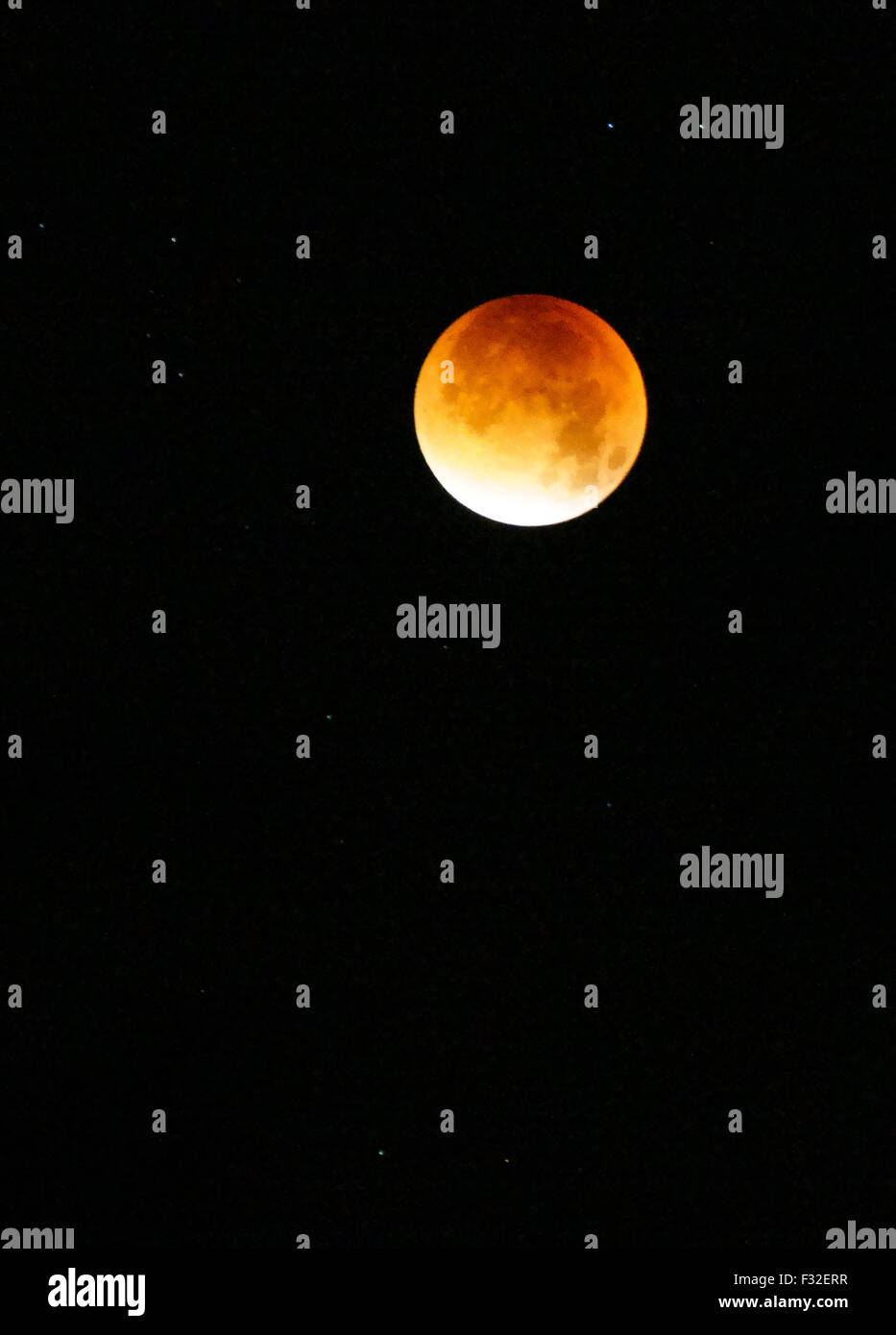 Godalming, UK. 28th Sep, 2015. The moon turns an orange colour during a lunar eclipse seen over Godalming in Surrey, Stock Photo