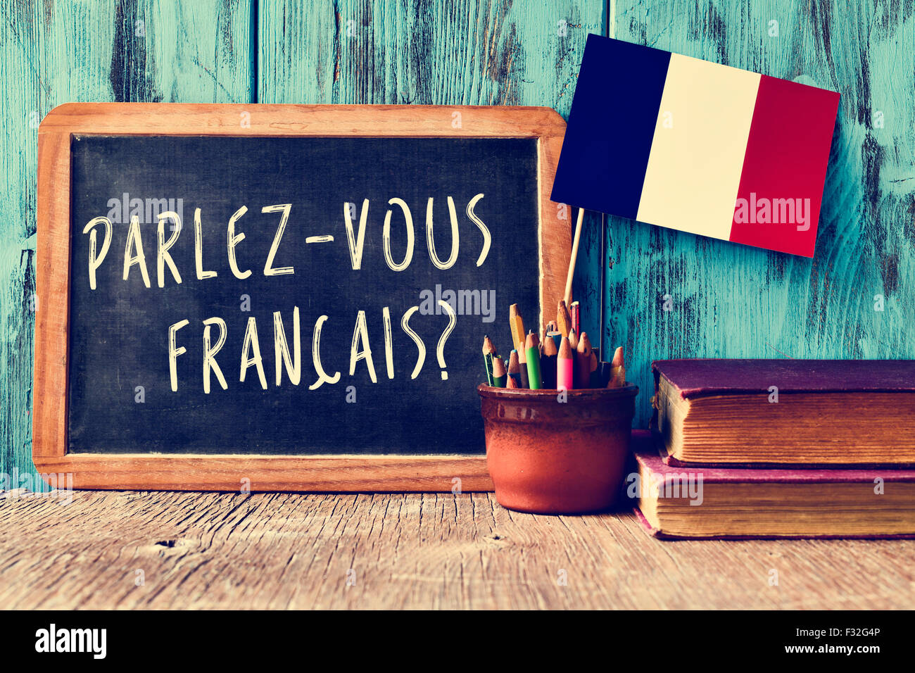 a chalkboard with the question parlez-vous francais? do you speak french? written in french, a pot with pencils Stock Photo