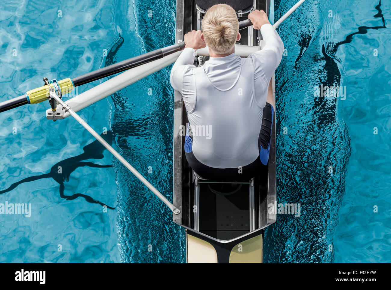 Top view of athletic competition rower, who strokes his  paddle through metallic blue water. - Stock Image