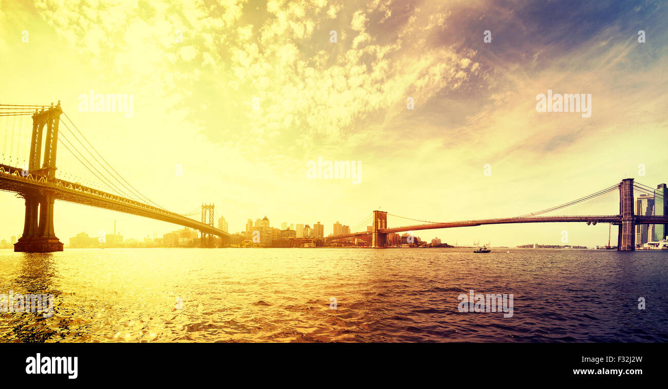 Vintage toned dramatic sunset over New York, panorama with famous Brooklyn Bridge and Manhattan bridge, USA. - Stock Image