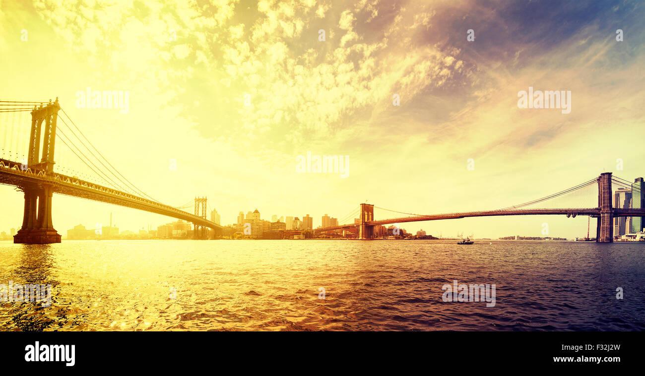 Vintage toned dramatic sunset over New York, panorama with famous Brooklyn Bridge and Manhattan bridge, USA. - Stock Image