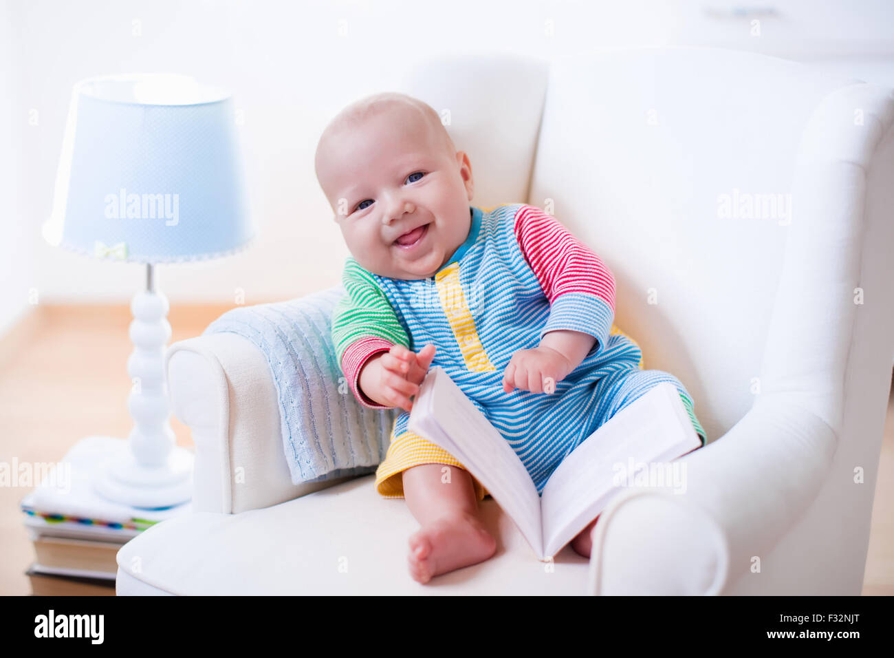 Cute Funny Baby Boy Reading A Book Sitting In A White Chair