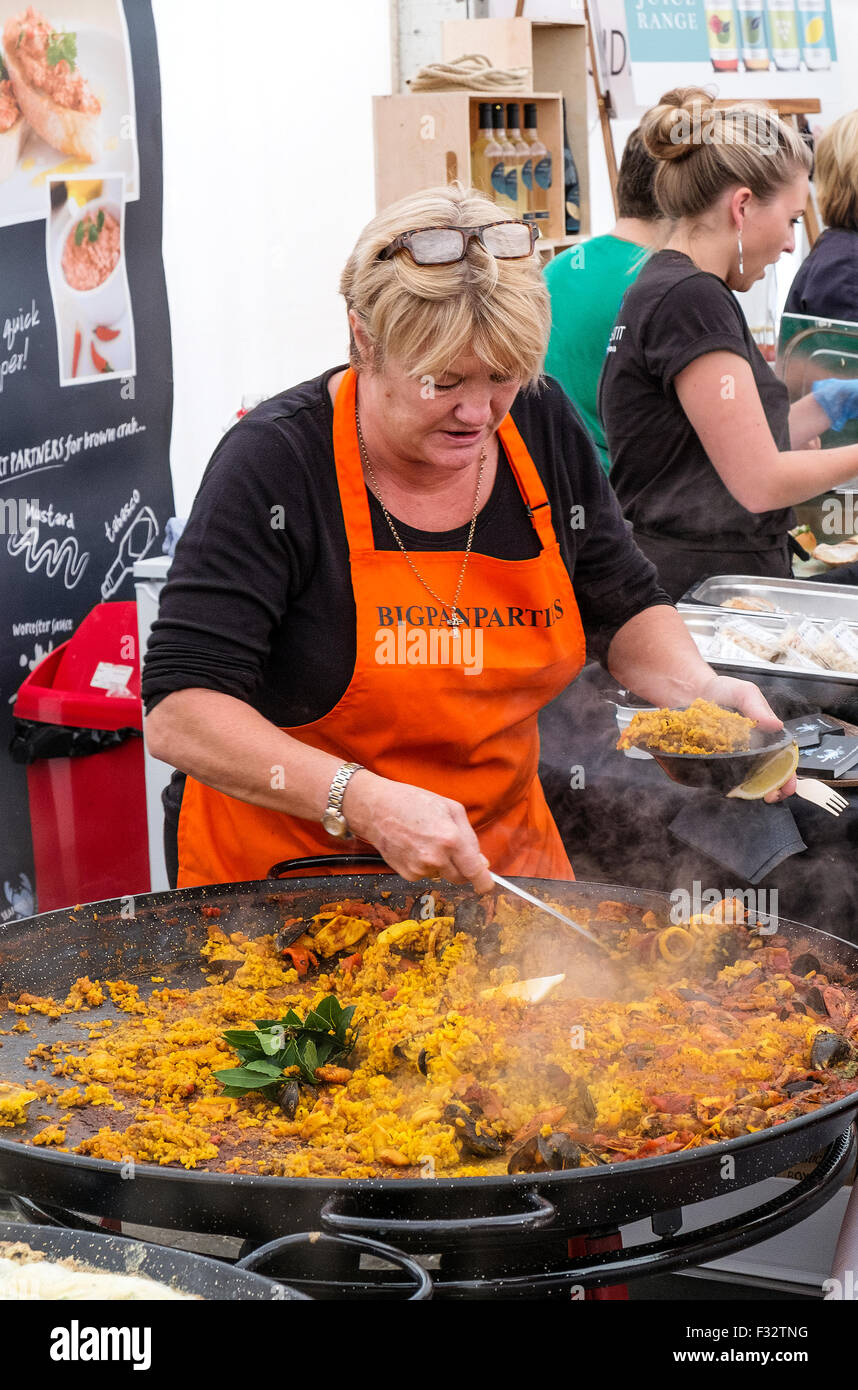 Paella being served from a huge pan at the Cornish food festival in Truro, Cornwall, UK - Stock Image