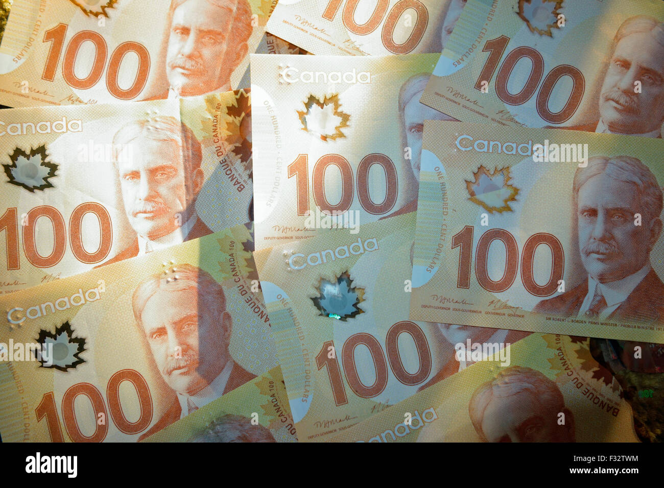 A collection of new Canadian 100 dollar bank note bills money - Stock Image