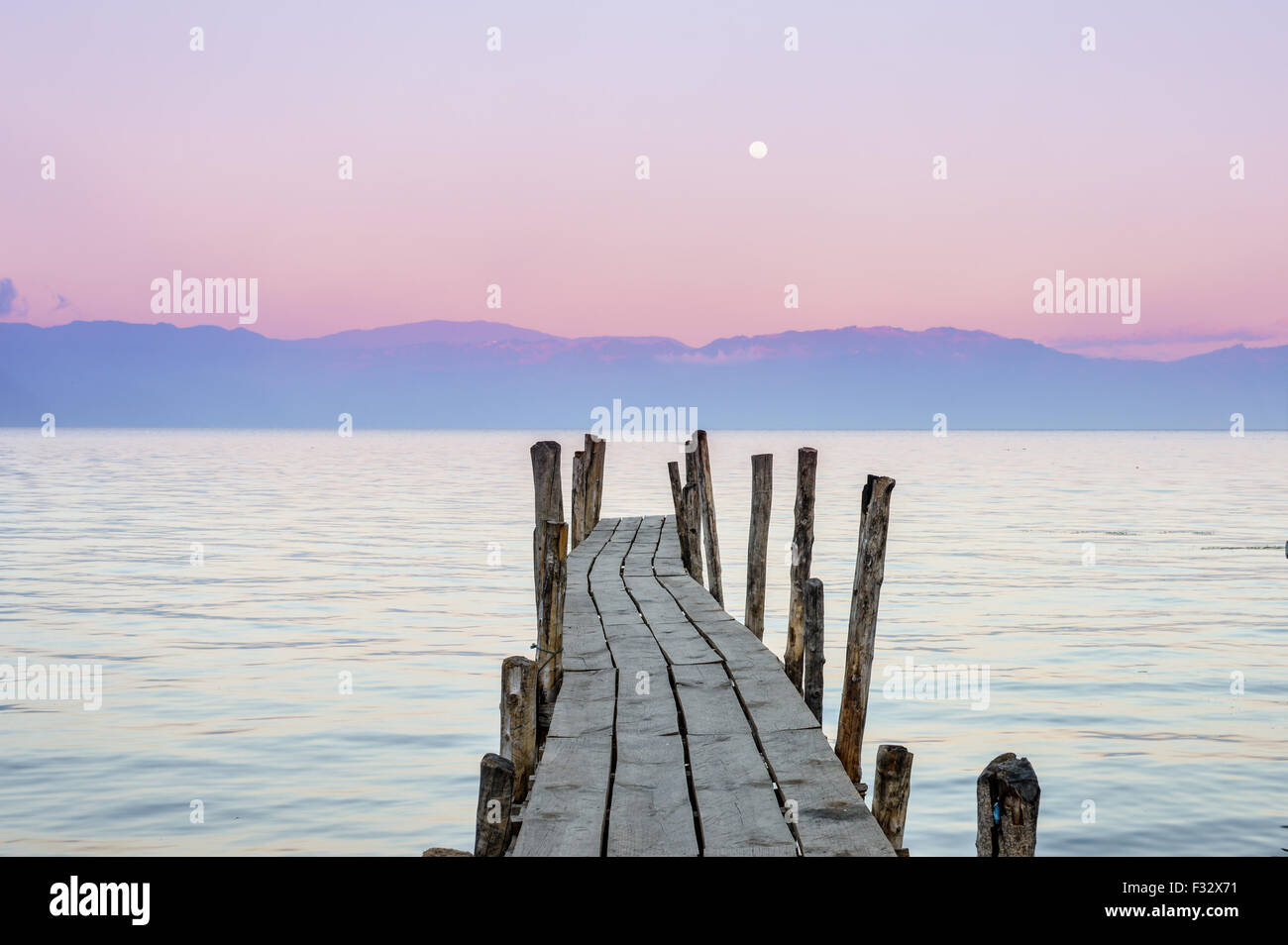 Little wooden boat dock with the pink sunset sky on the background in Lake Atitlan, Guatemala - Stock Image