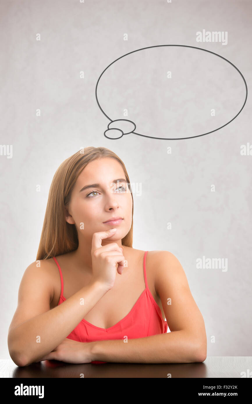 Woman thinking in grey background with a bubble over her head - Stock Image