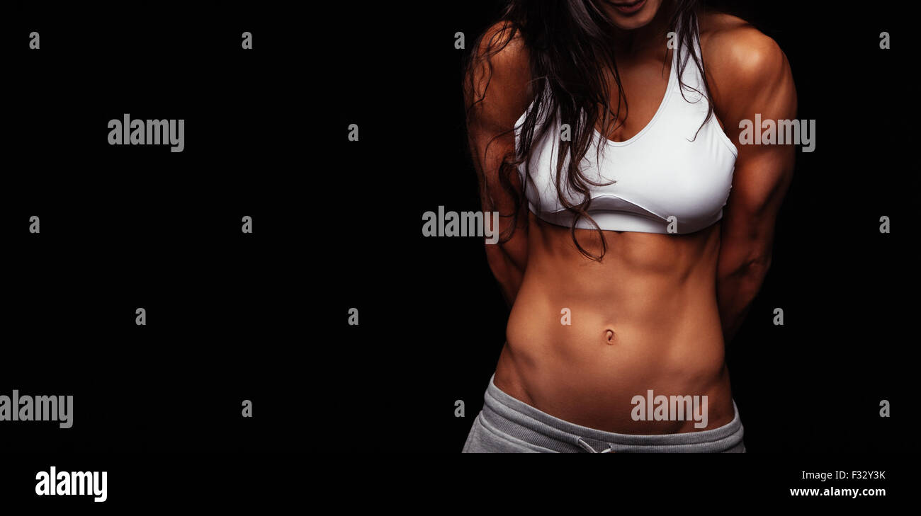 Close up of young woman's torso. Perfect abdomen muscles of a female athlete on black background with copyspace. - Stock Image