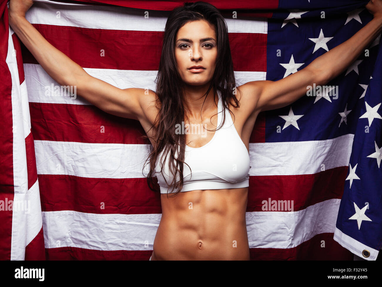 Portrait of proud female athlete holding American Flag against. Muscular young woman looking confidently at camera. - Stock Image