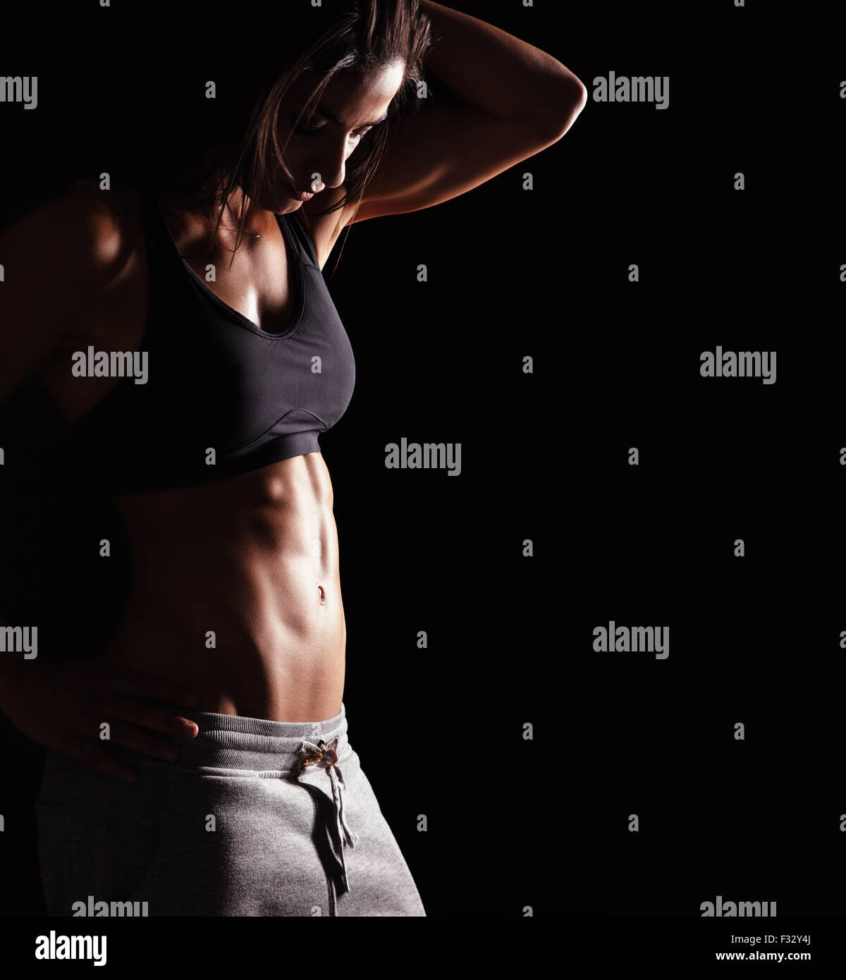 Image of fitness woman in sports clothing looking down young female model with muscular body horizontal studio shot with copy