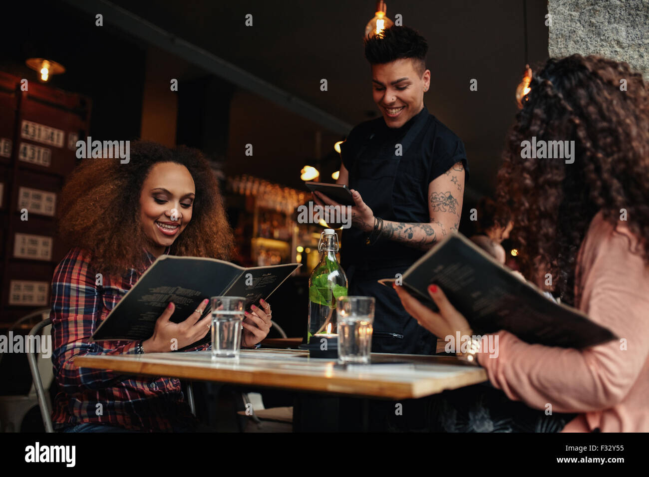 Young women seated at a table holding menus in a restaurant. Young girls at cafe making  choice and place their - Stock Image