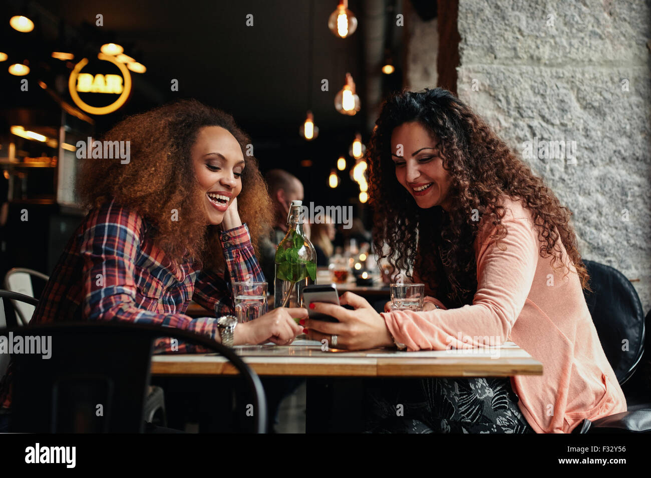 Young women sitting at cafe and using phone. Friends sitting in a restaurant with one woman showing something interesting - Stock Image