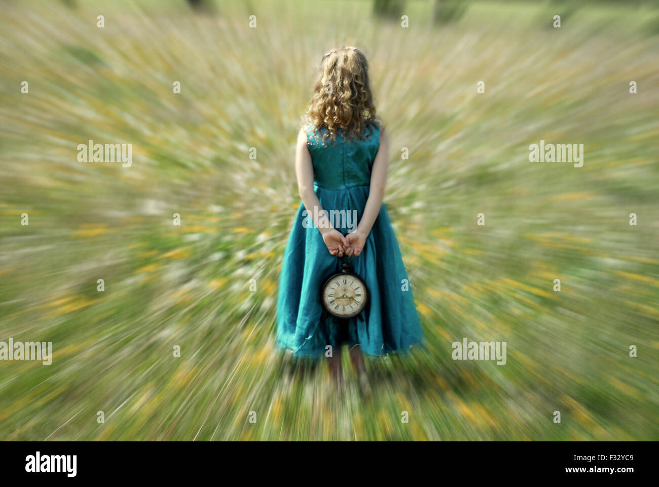 zoom effect little girl with clock in her hands blue dress wonderland - Stock Image