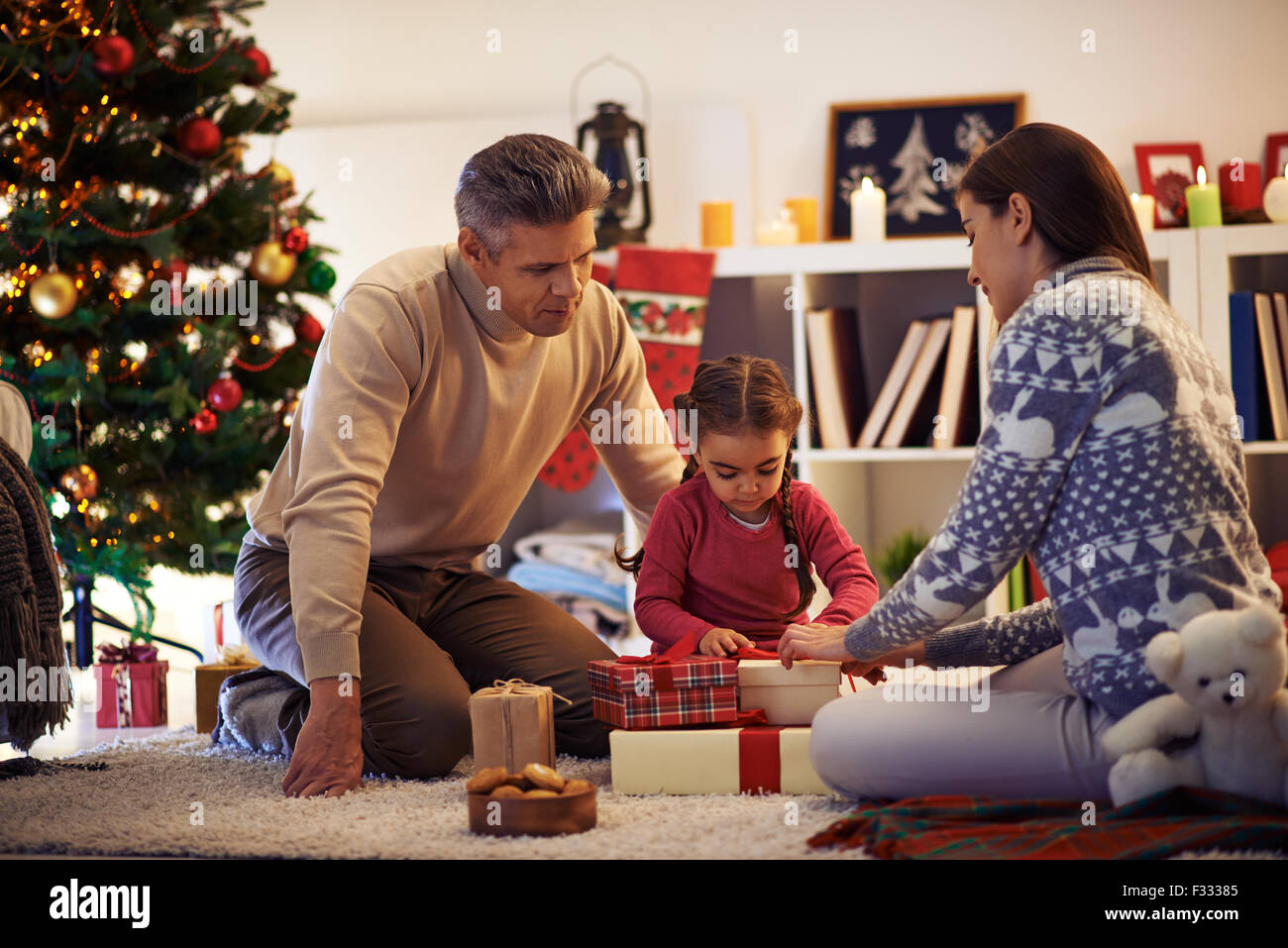 Family of three packing gifts and tying knots on tops of boxes before Christmas - Stock Image