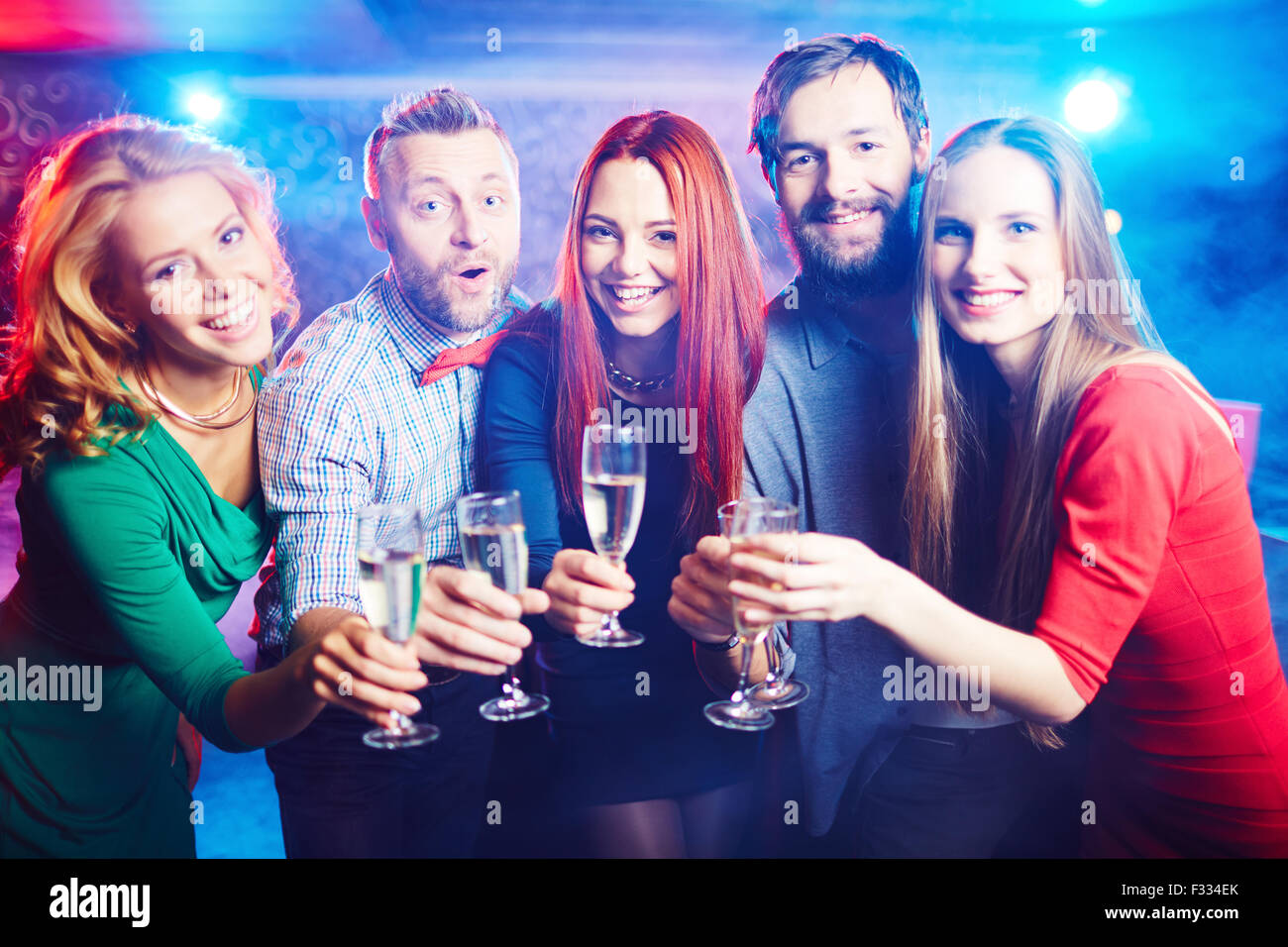 Group of ecstatic friends having party in night club - Stock Image