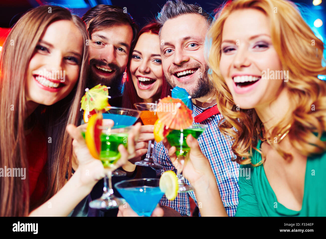 Ecstatic young people with cocktails cheering at party - Stock Image