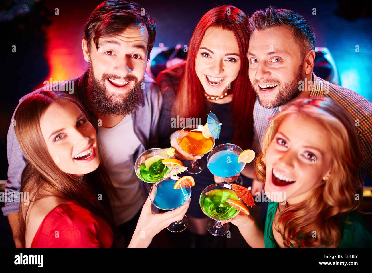 Ecstatic guys and girls toasting at party and looking at camera - Stock Image