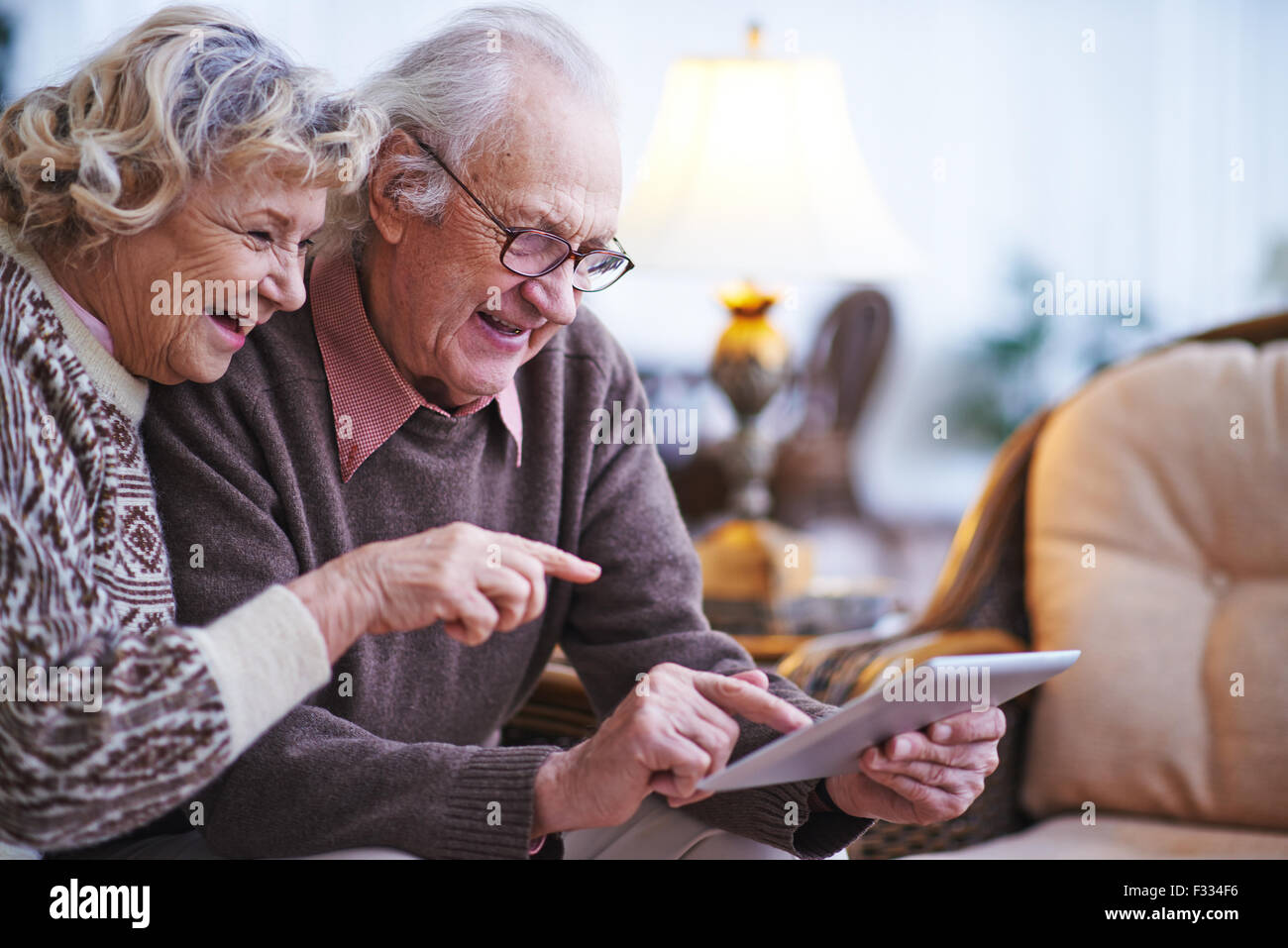 Happy senior couple using touchpad at home - Stock Image