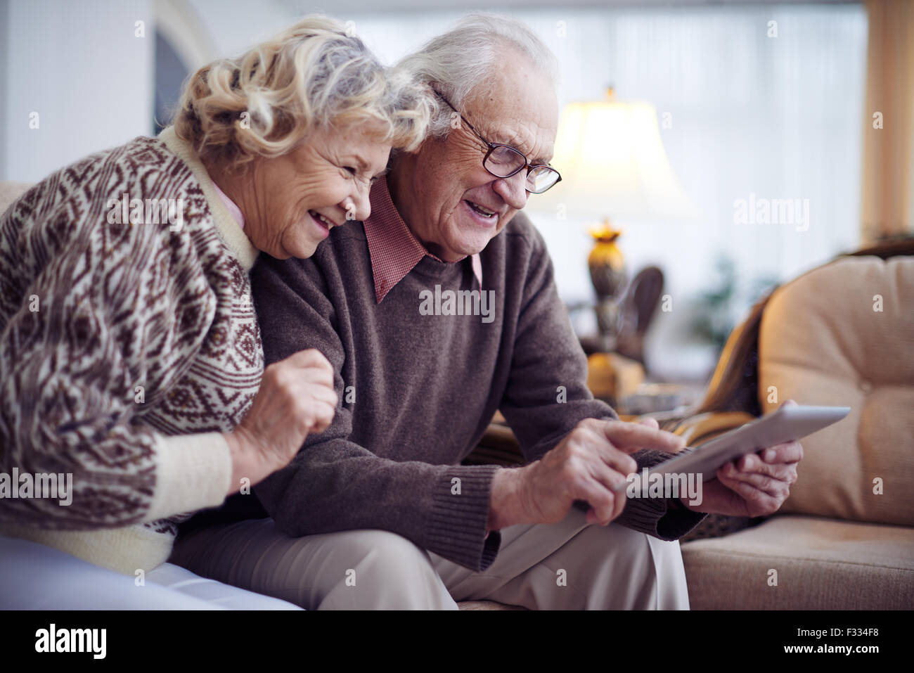 Happy aged couple with touchpad networking at home - Stock Image
