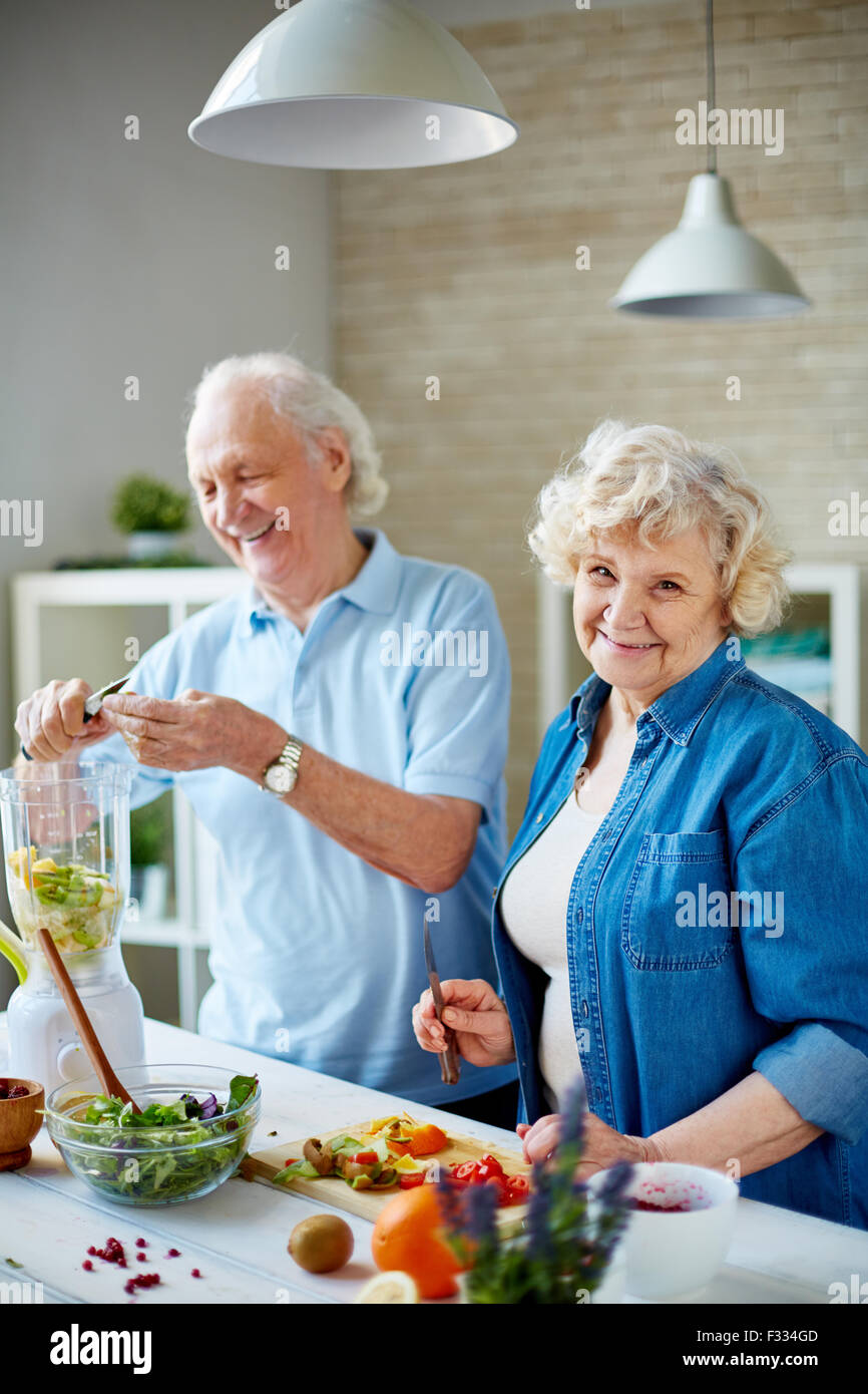 Happy seniors cooking vegetarian food in the kitchen - Stock Image