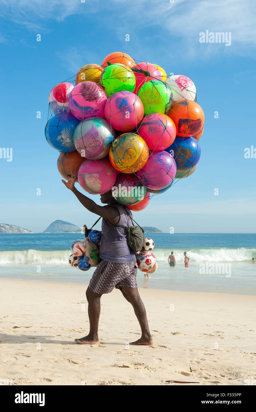 RIO DE JANEIRO, BRAZIL - JANUARY 20, 2013: Beach vendor selling colorful beach balls carries his merchandise along - Stock Image
