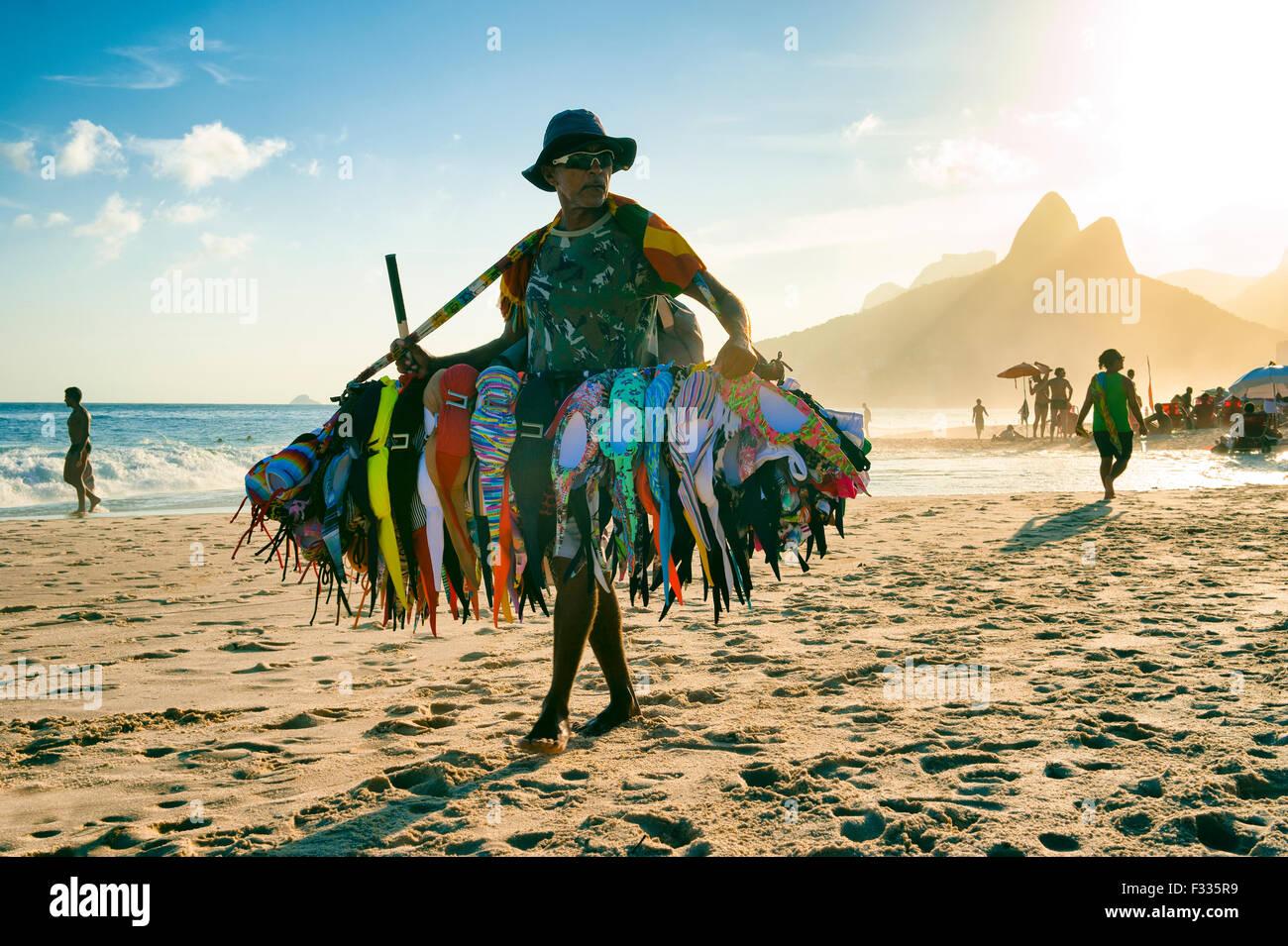 RIO DE JANEIRO, BRAZIL - JANUARY 20, 2013: Vendor selling bikini bathing suits walks on Ipanema Beach during a misty - Stock Image