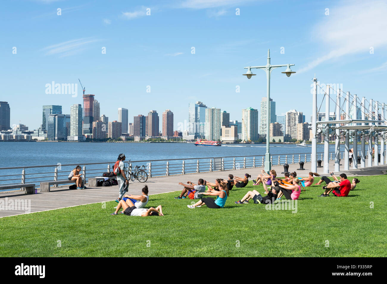 NEW YORK CITY, USA - AUGUST 29, 2015: Personal trainer leads group boot camp fitness class near the Hudson River. - Stock Image