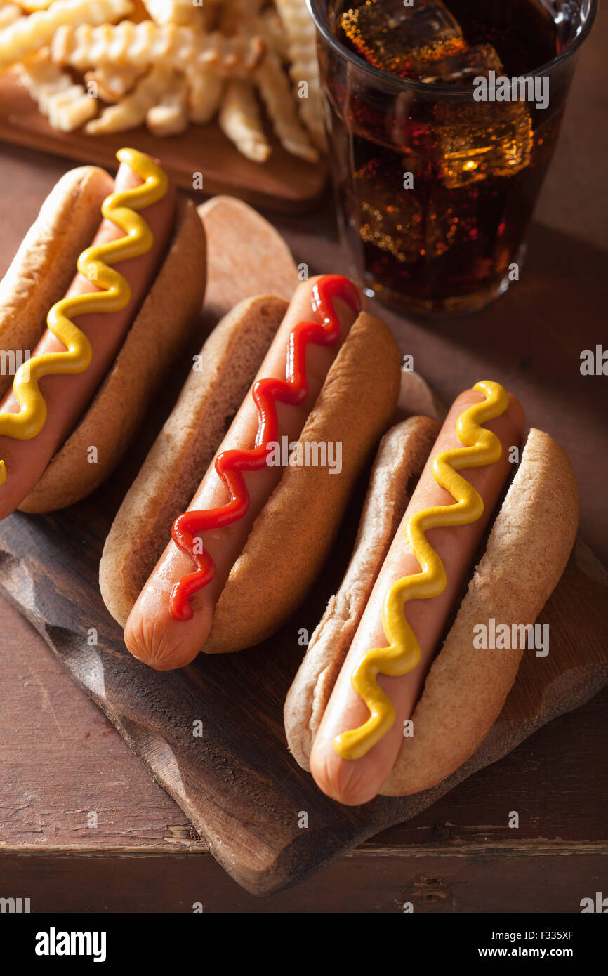 grilled hot dogs with mustard ketchup and french fries - Stock Image