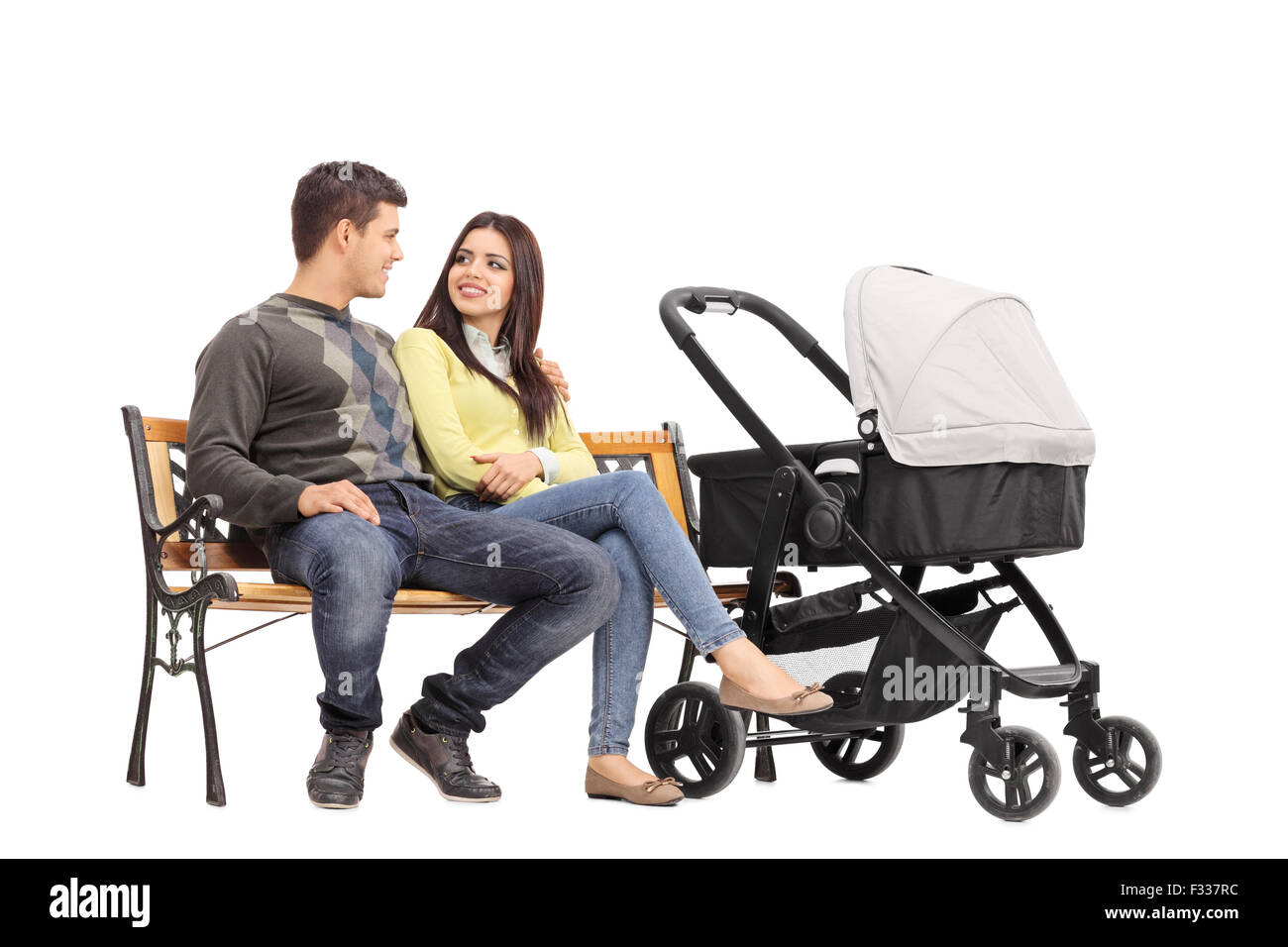 Young parents sitting on a bench and talking to each other with a baby stroller next to them isolated on white background - Stock Image
