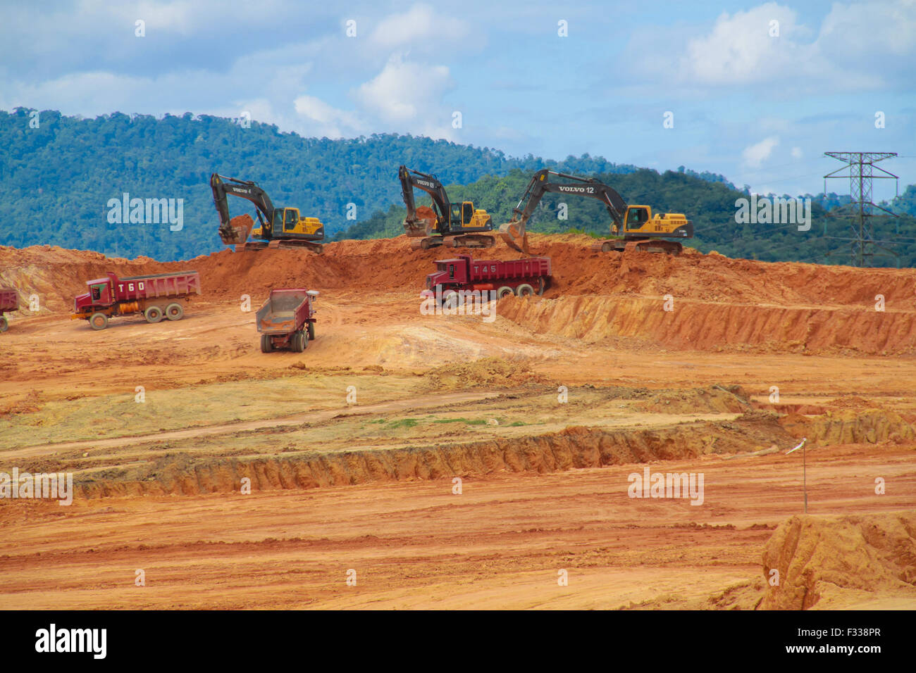 Earth movers and trucks at work. - Stock Image
