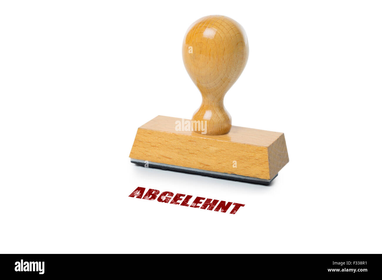 Abgelehnt (German: denied) printed in red ink with wooden Rubber stamp isolated on white background - Stock Image