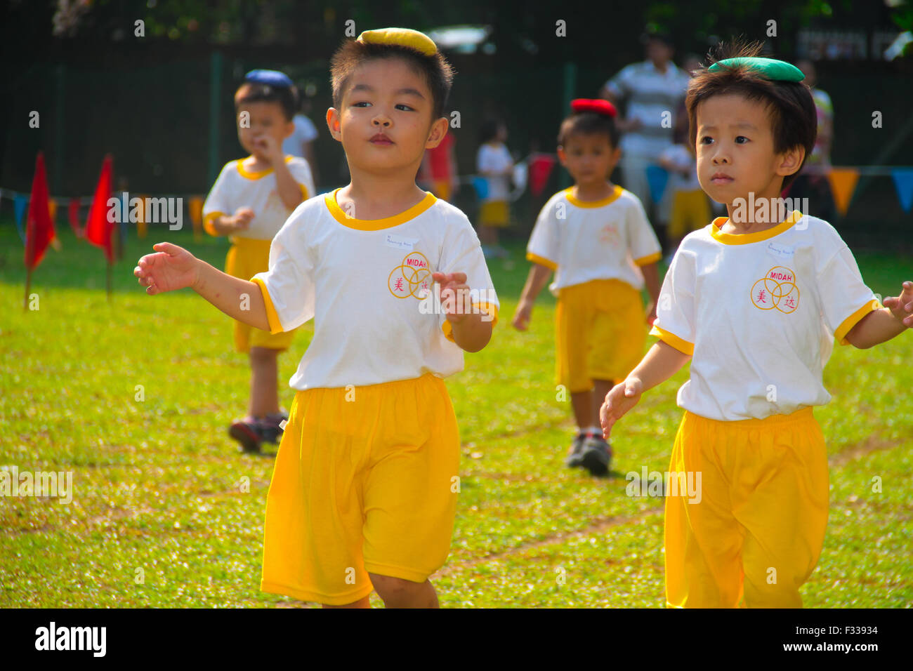 Kindergarten children competing in balancing bean bag race at their sport day. - Stock Image