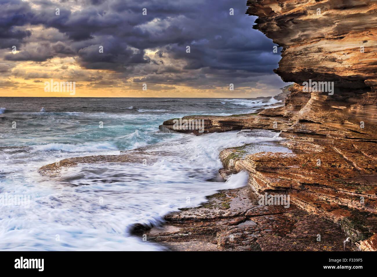 pacific ocean endless waves undermining sandstone rocks of Australian coast near Sydney during stormy sunrise - Stock Image