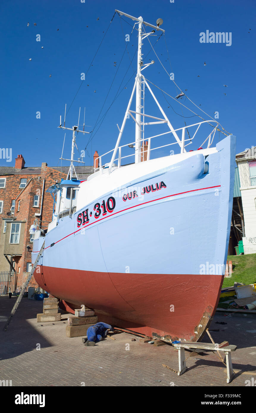 Wooden fishing boat being repainted, Bridlington East Yorkshire Stock Photo