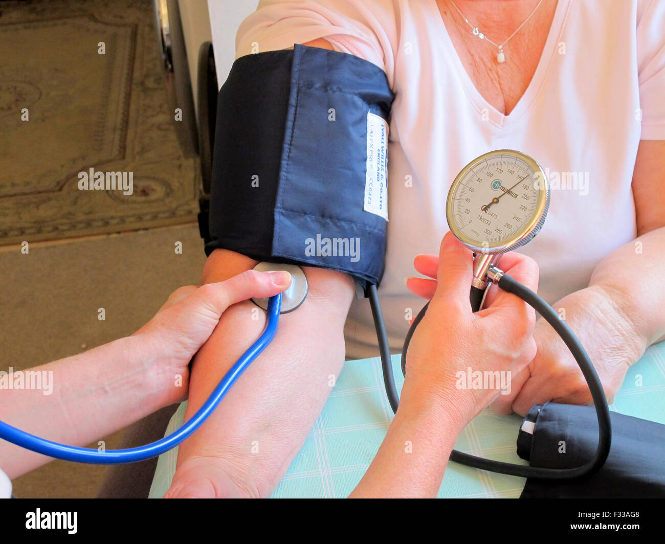 SUTTON-IN-ASHFIELD, NOTTINGHAMSHIRE, UK. JUNE 24, 2015. A care nurse taking a stroke patient's blood pressure - Stock Image