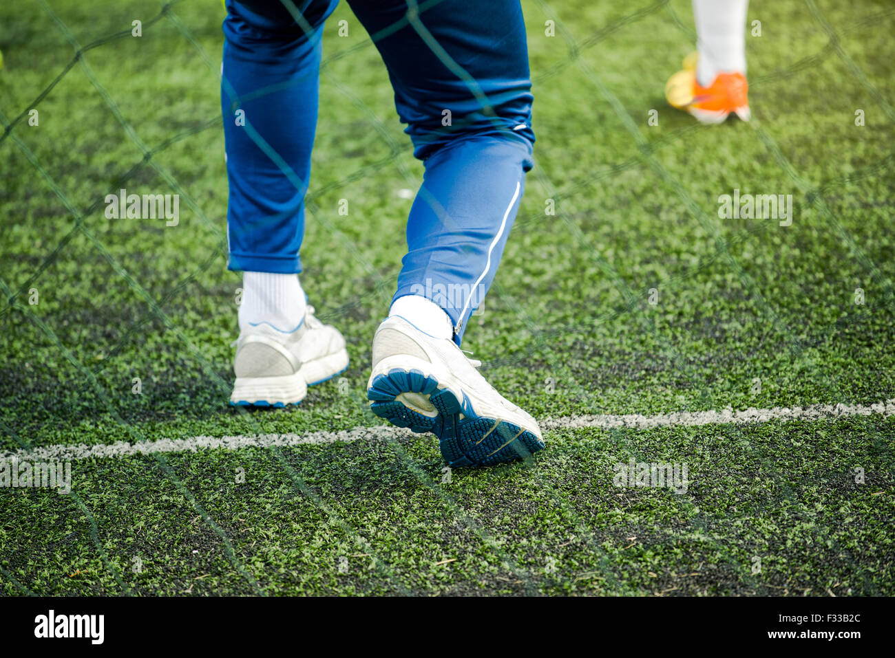 Kids soccer coach on football pitch training kids in sports tactics - Stock Image