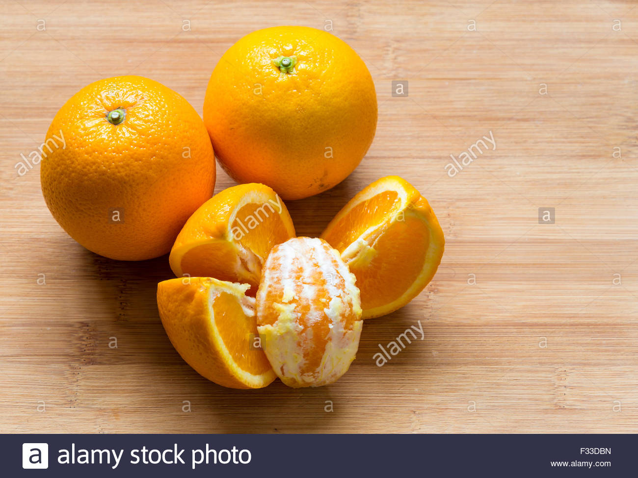 Oranges placed on a wooden chopping board. There are two whole oranges and four quarter cut pieces with one peeled - Stock Image
