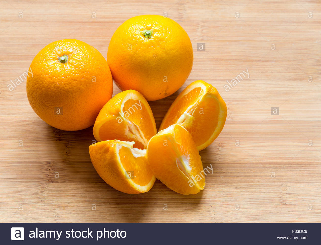 Oranges placed on a wooden chopping board. There are two whole oranges and four quarter cut pieces. - Stock Image