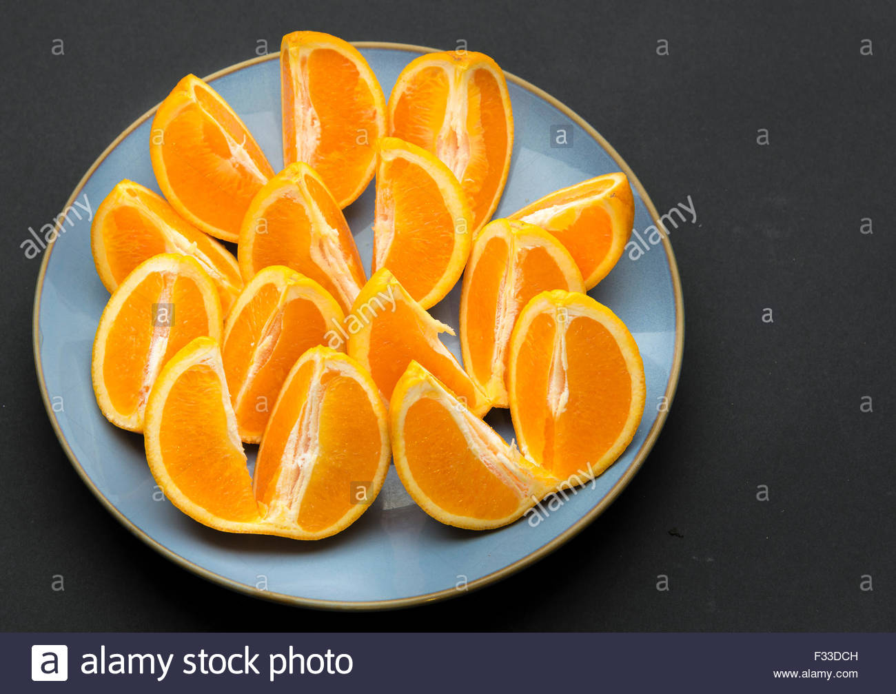 Quarter cut and unpeeled pieces of orange fruit arranged on a round blue plate in black background. - Stock Image