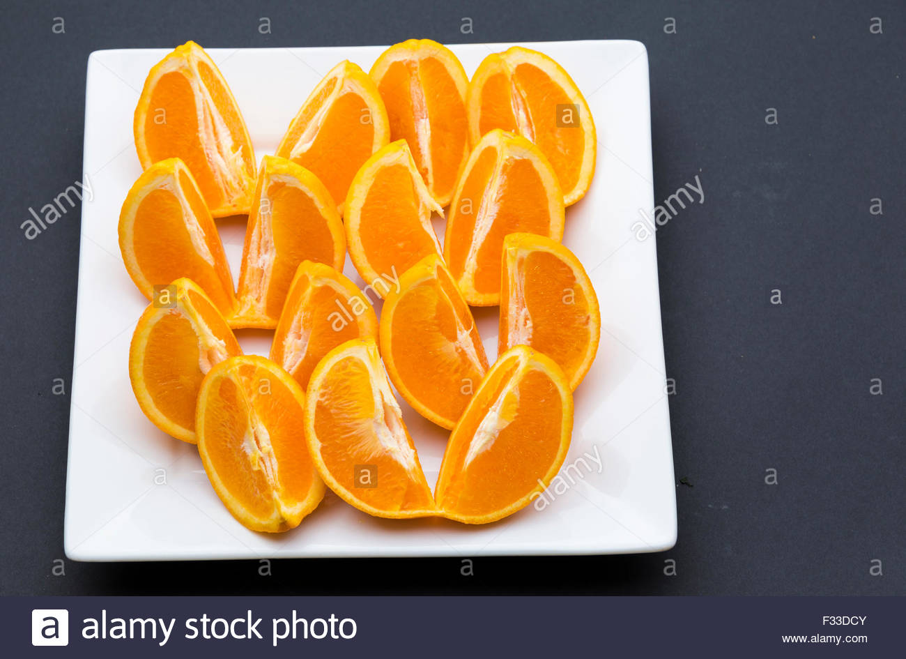 Quarter cut and unpeeled pieces of orange fruit arranged on a square white plate in black background. - Stock Image