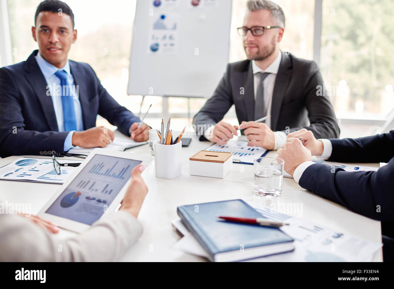 Business team gathered by workplace for consultation - Stock Image