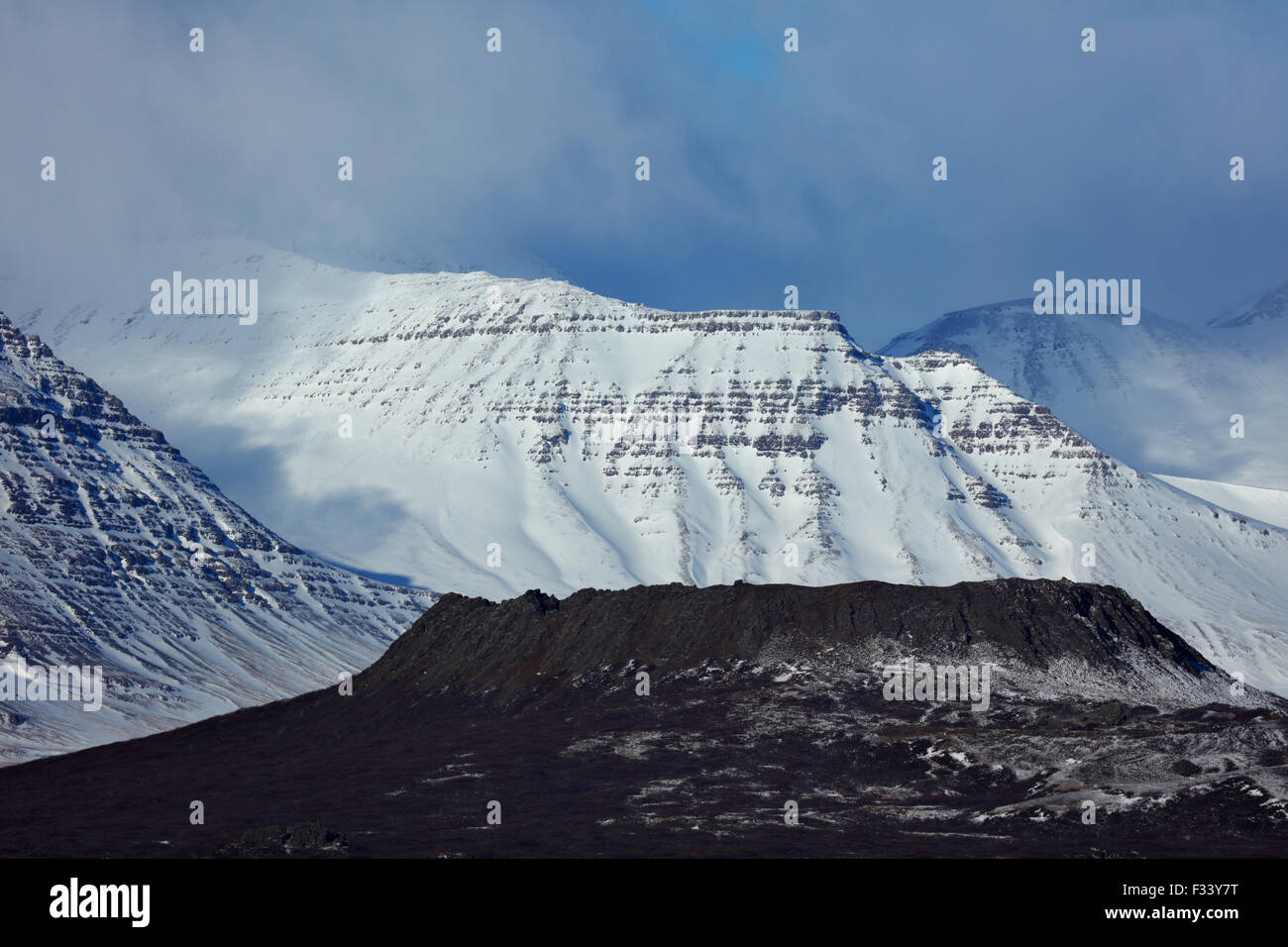 the Eldborg volcanic crater with snowclad Hafursfell beyond, Snaefellsness Peninsula, Iceland - Stock Image