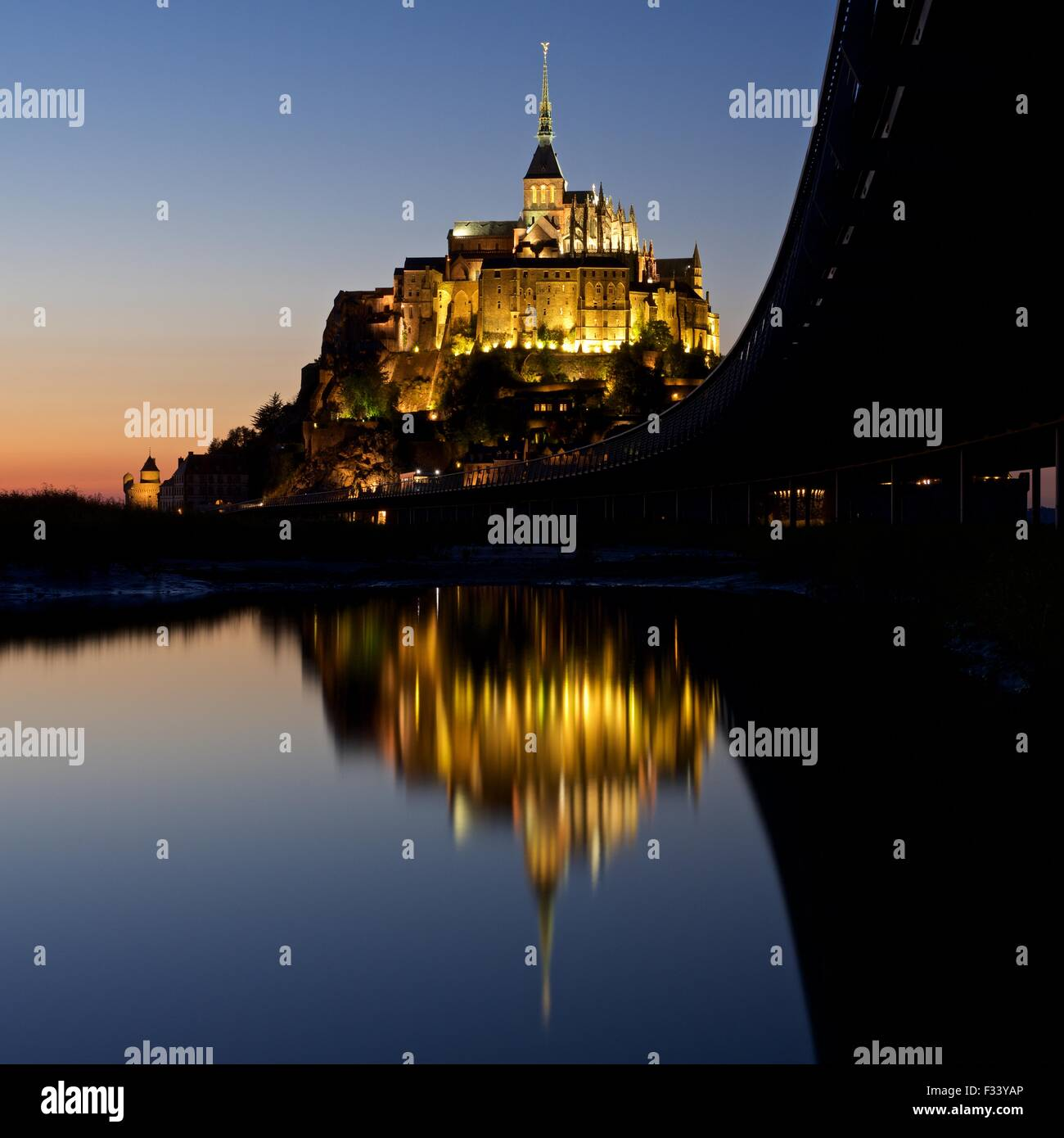 A colour image of reflections of Mont Saint Michel lit up at dusk in a water pool on the beach at Mont Saint Michel - Stock Image