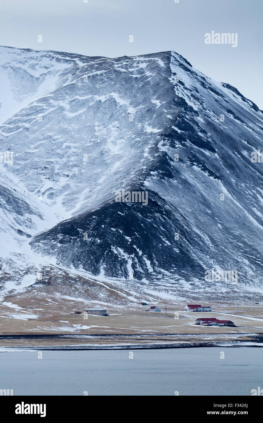 a farm at the foot of snowclad Kolgrafamuli, Snaefellsness Peninsula, Iceland - Stock Image
