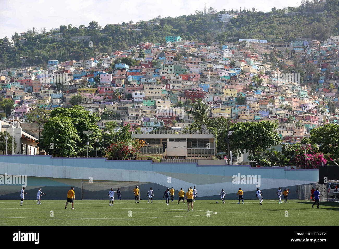 Adults play soccer at the Park Sainte Therese soccer field with colorful homes along the hillside September 15, - Stock Image