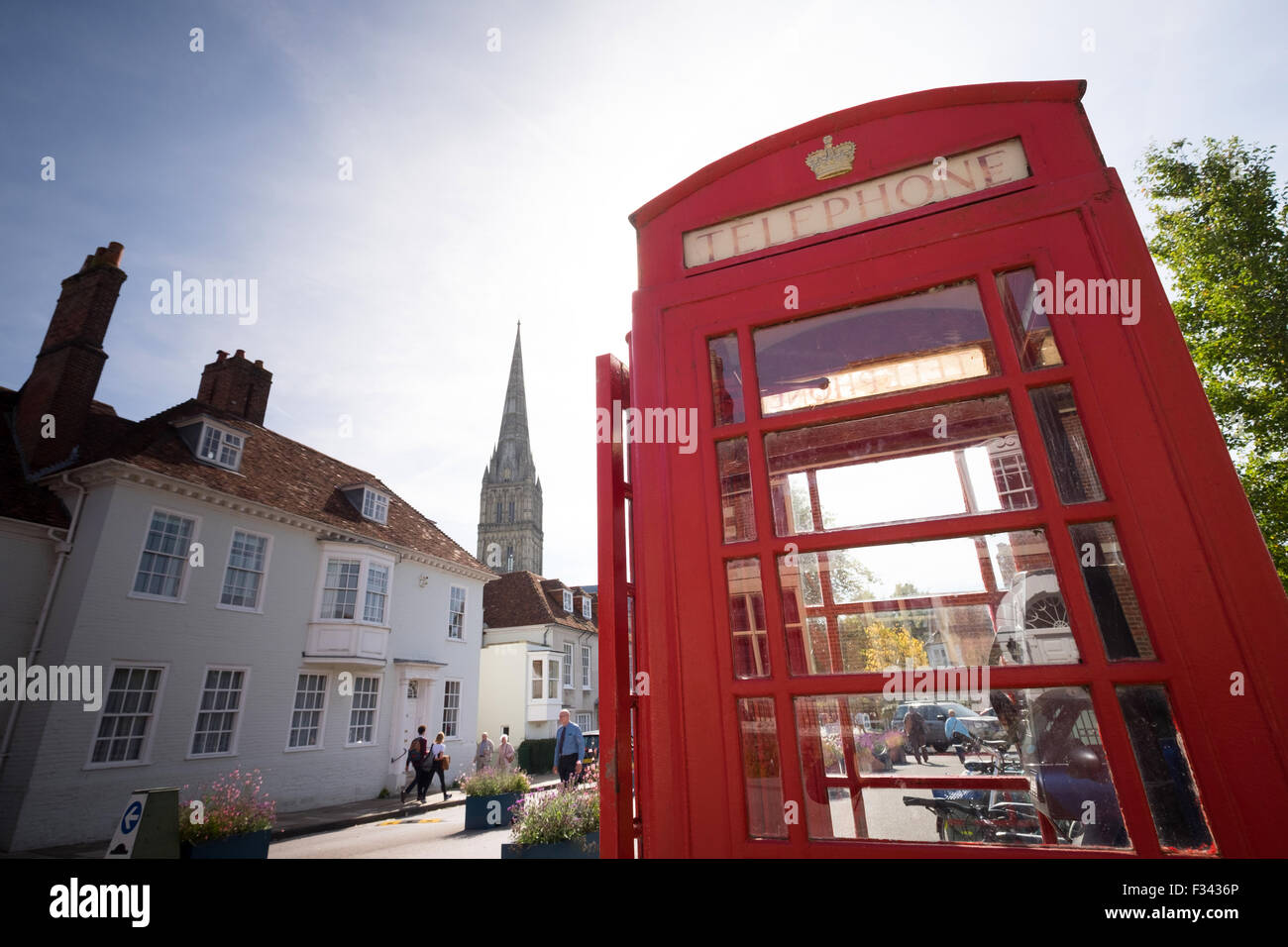 Traditional red telephone box pictured in Salisbury with the cathedral in the background - Stock Image