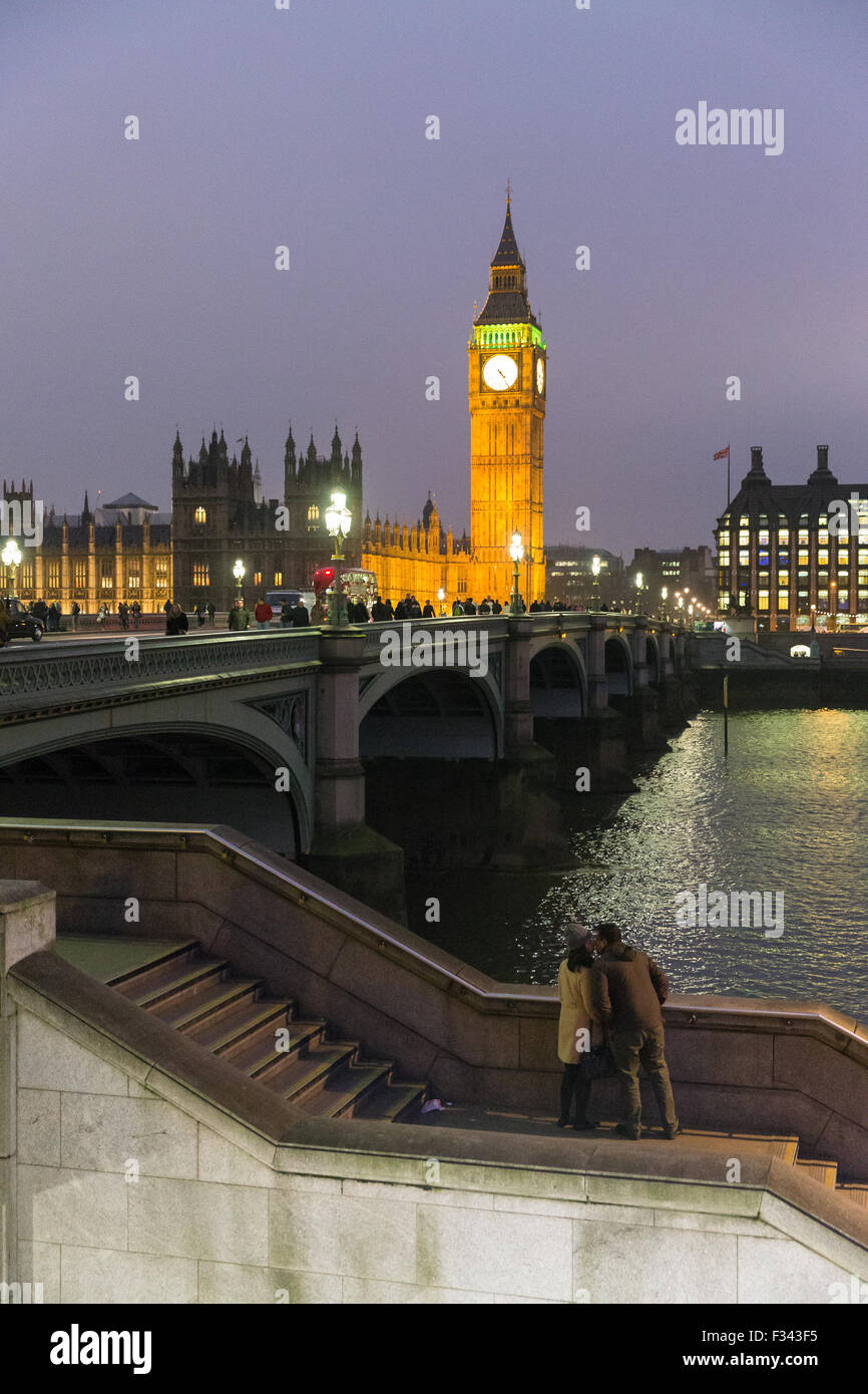 a couple kissing at dusk on the Embankment with Big Ben, the Palace of Westmintster and the River Thames beyond, - Stock Image