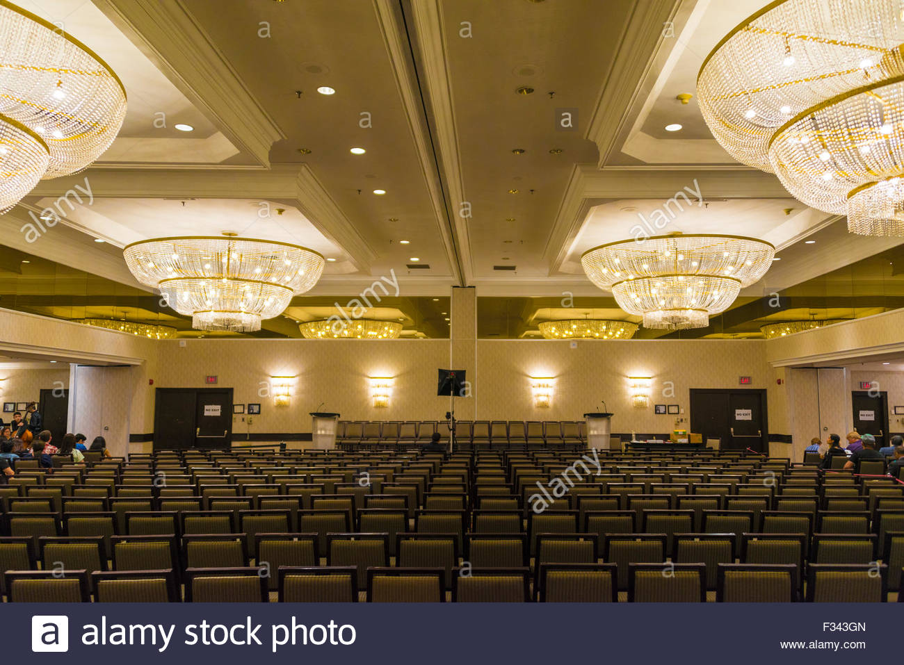 Conference hall with big chandeliers and several rows of vacant conference hall with big chandeliers and several rows of vacant chairs there is a dais with chairs and two podium few people se mozeypictures Choice Image