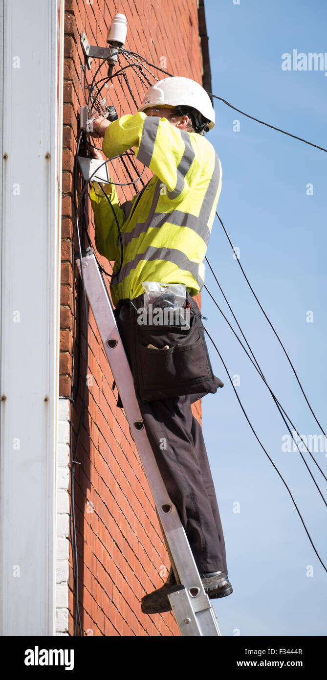2820f06d12f0 A BT Openreach engineer working up a ladder fixing a phone line - Stock  Image